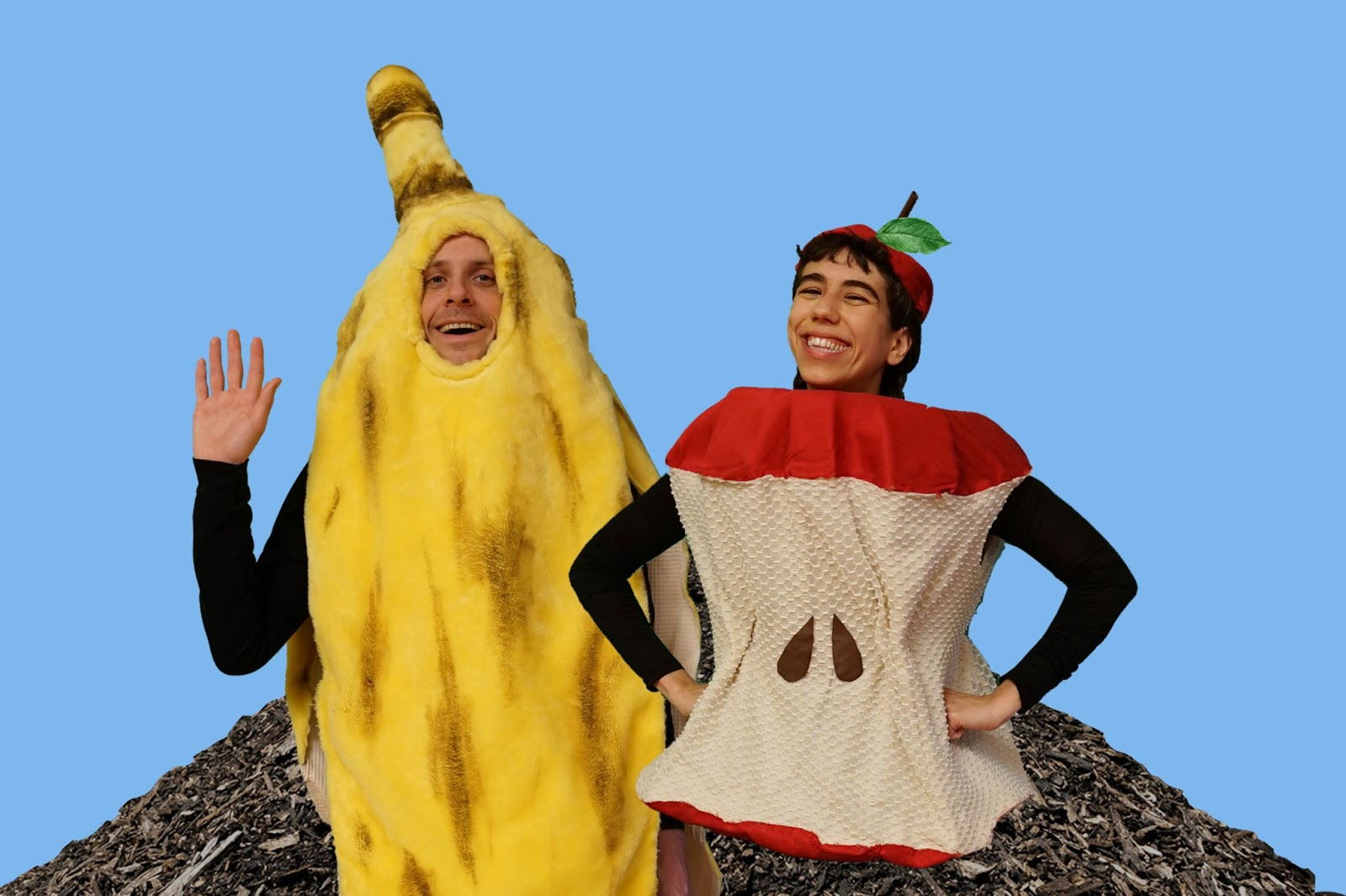 One person dressed as a banana and one person dressed as an apple core