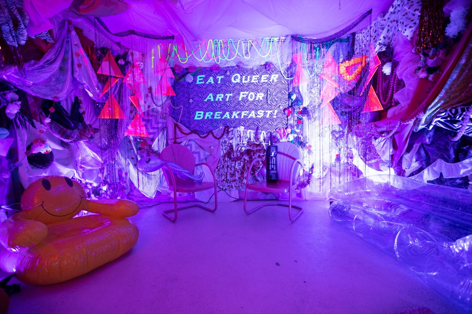 """Purple tinted room with a sign that says """"Eat Queer for Breakfast"""""""
