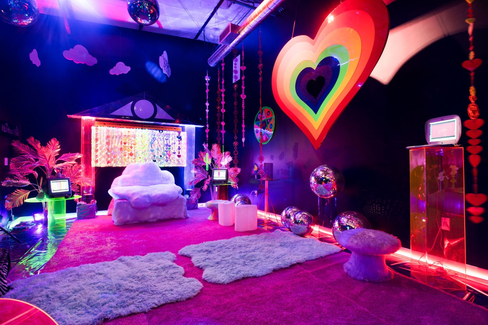 Room filled with a giant rainbow heart and disco balls on the ceiling