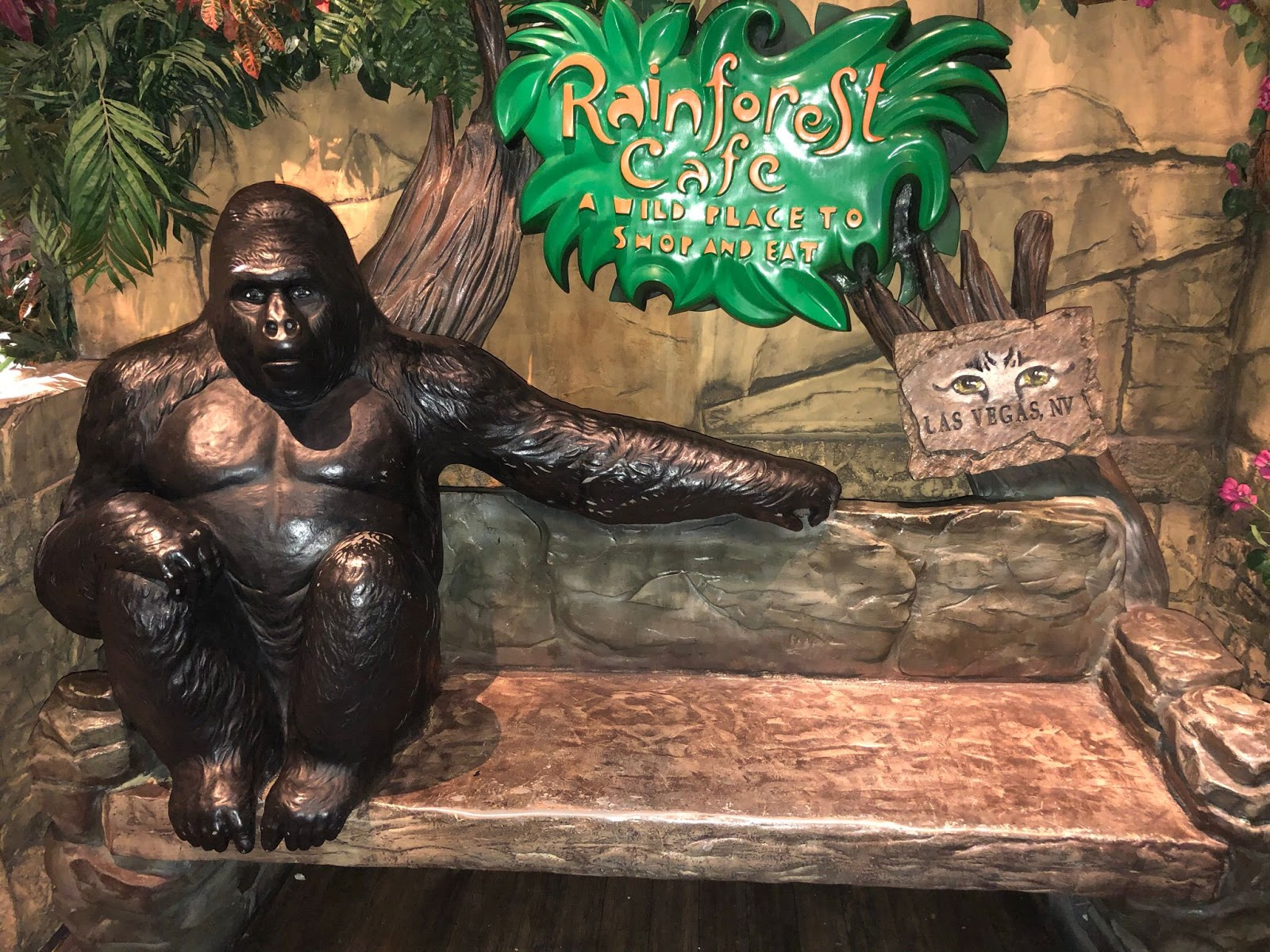 """The entrance to Rainforest Cafe features a large brown bench that gives the impression that it's cut from wood. A large black gorilla sits to the left on the bench with his left arm draped across the back of the bench, inviting guests to sit next to him. Behind the bench, there is a bright green sign that reads """"Rainforest Cafe: A Wild Place to Shop and Eat"""" in yellow writing. To the right of the green sign, there is a smaller brown sign that says Las Vegas, Nevada. A pair of mysterious cat eyes sit just above the city name."""