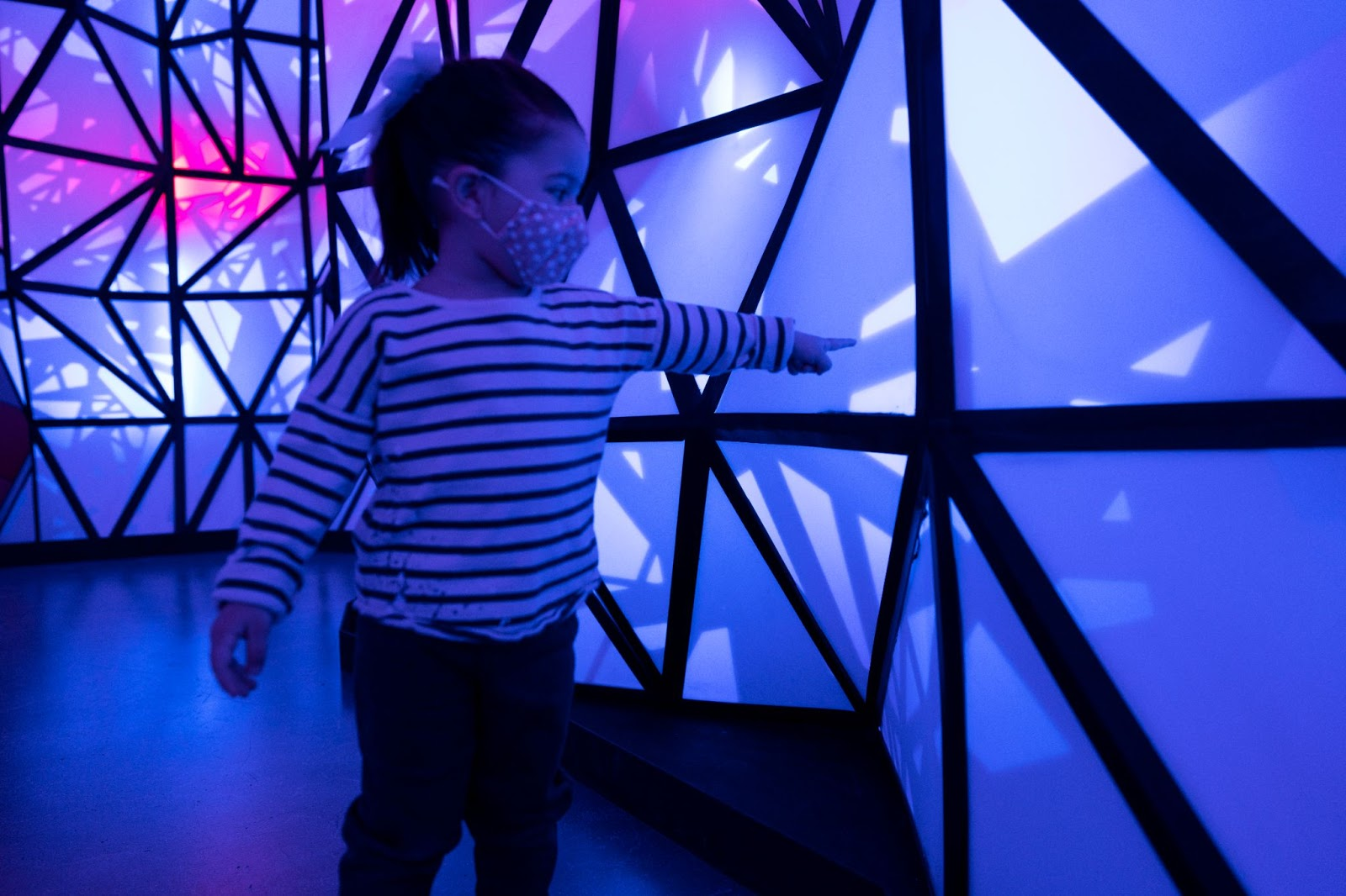 a small female toddler in a mask reaches out with one finger to touch a blue, triangular art structure