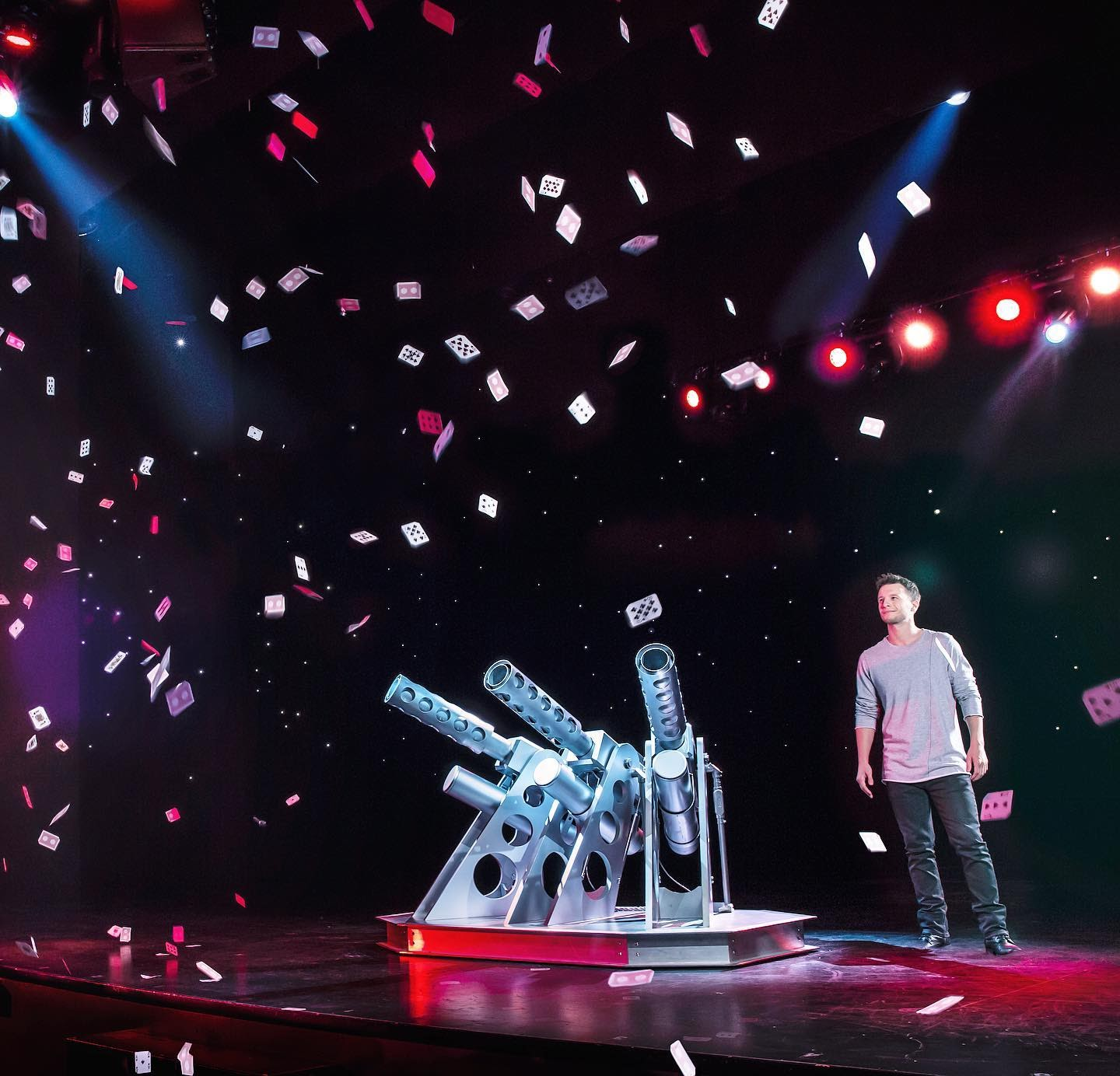 Vegas magician Mat Franco stands on the stage with a backdrop of stars behind him. A cannon with three funnels is next to him and dozens of cards shoot from the cannon and fly into the audience.