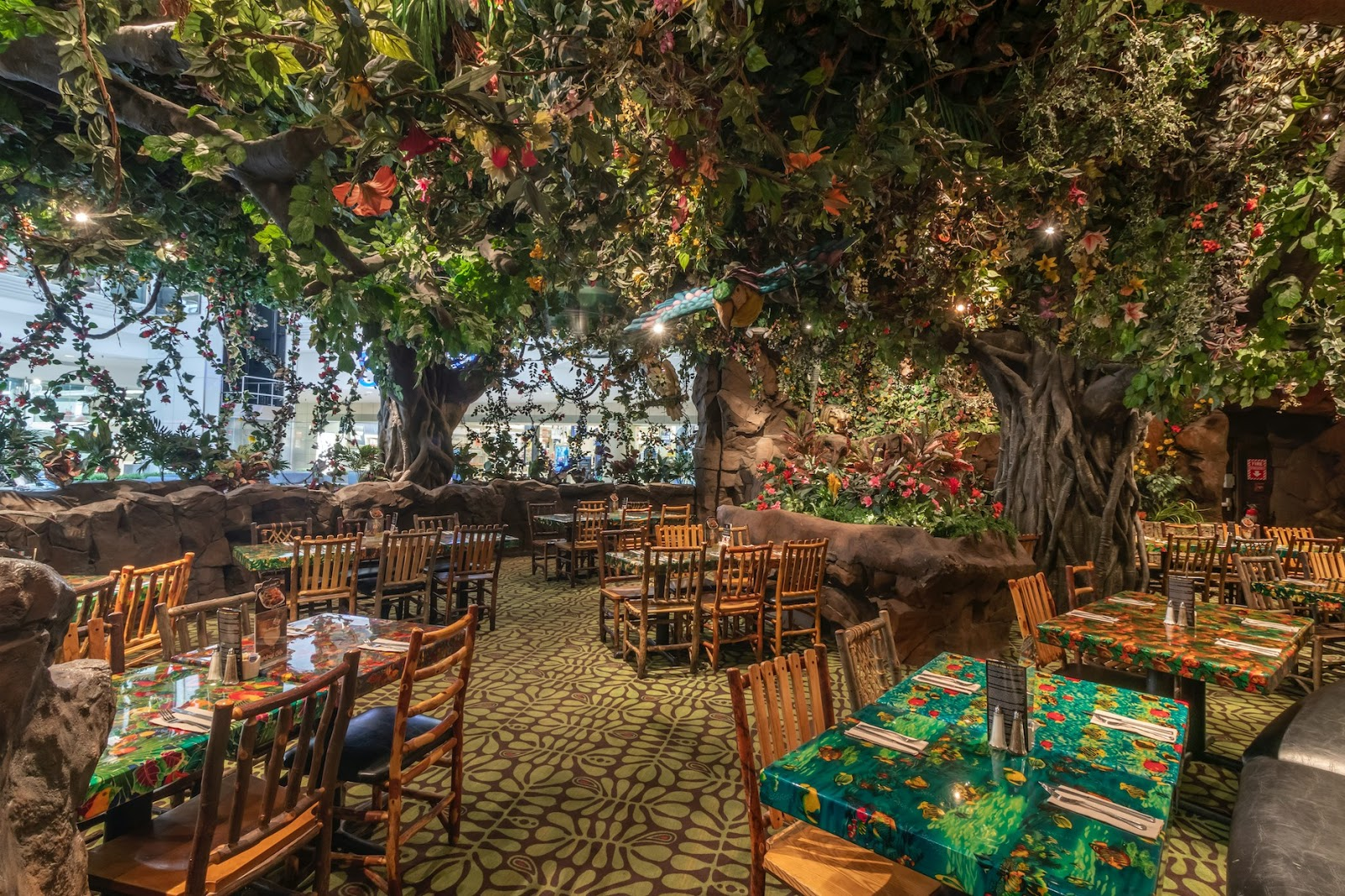 A wide photo of the Rainforest Cafe dining area. There are several large tables, surrounded by lush trees that have fake butterflies and birds hanging from their branches.