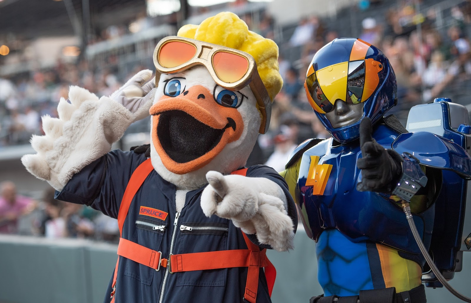Two costumed characters stand on the Las Vegas ballpark baseball field and point to the camera. Spruce the Goose is dressed in a dark blue and orange air pilot's jumpsuit. He is using one hand to point at the camera and the other to lift his large orange glasses to reveal his bright blue eyes. The character to the right is The Aviator who is in a blue, yellow and orange costume pointing at the camera. He wears a reflective helmet and a parachute back on his back.