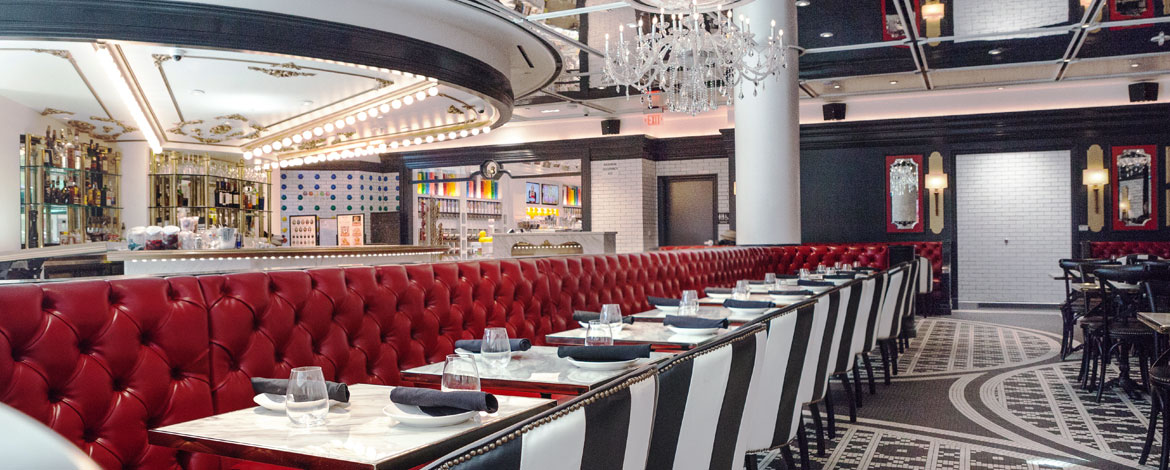 a wide photo of the large and lavish Sugar Factory dining room. There is a long red booth under a sparkling chandelier with black and white chairs on the other side of the table.