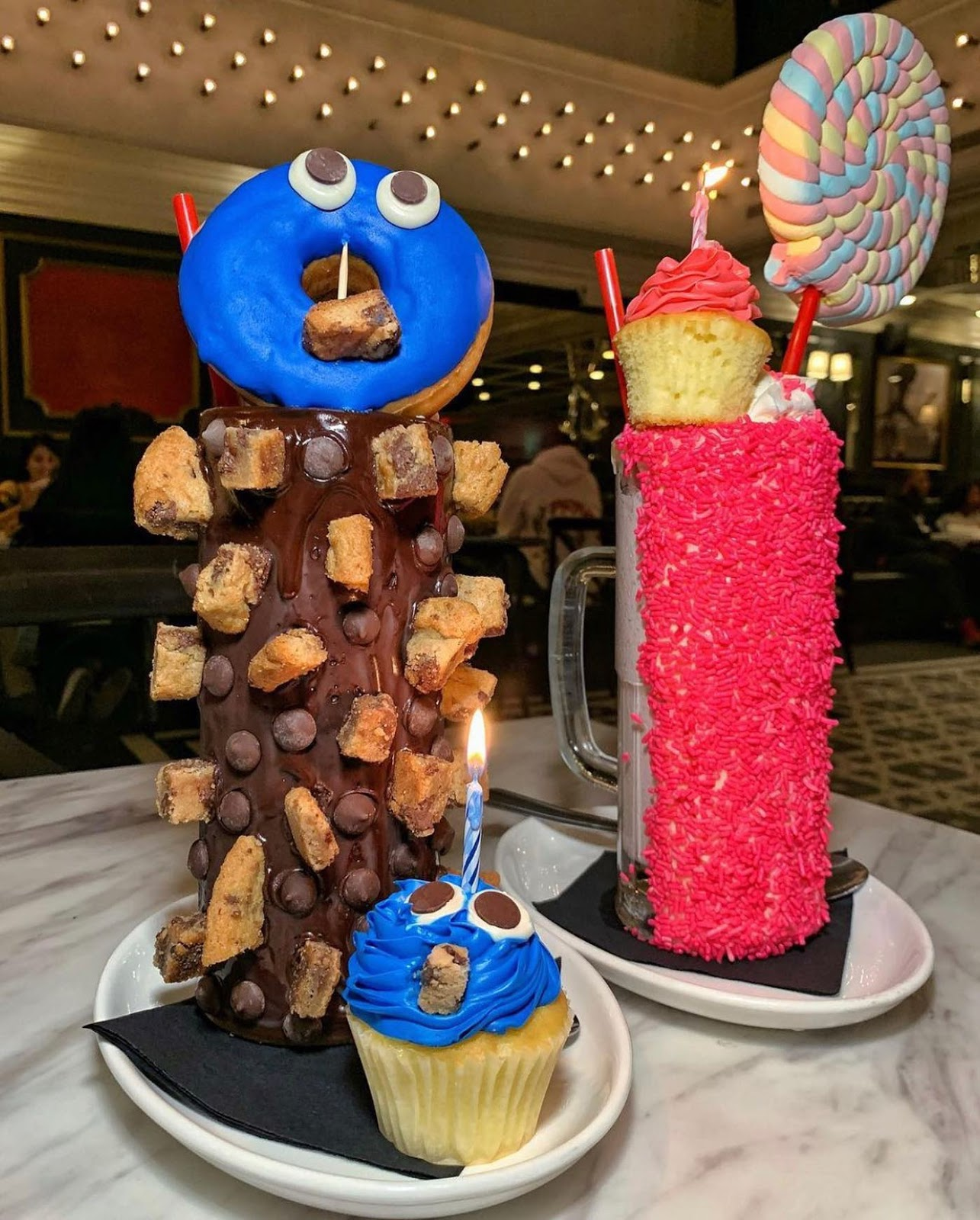 two large milkshakes sit atop a white granite table. The milkshake on the left, called the Cookie Monster Make a Wish, is tall and the glass is dipped in chocolate. It has cookie dough and chunks of cookie stuck in the chocolate on the outside. On top of the milkshake sits a circular donut with blue icing and two eyes to resemble Cookie Monster. Also on the plat is a vanilla cupcake with blue icing and two eyes. The milkshake on the right, The Princess Make a Wish, has a glass dipped in bright pink sprinkles. On top, there are two straws poking out next to an oversized pink lollipop and a vanilla cupcake with pink frosting.