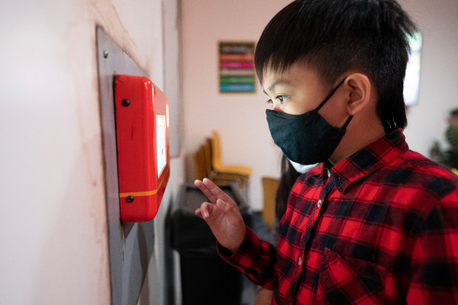 a young boy, approximately 6-8 years old in a red flannel button up shirt and a mask stands at a boop station in the employee micro-breakroom. His hand reaches out to touch the bright red boop station to take the cone color test.