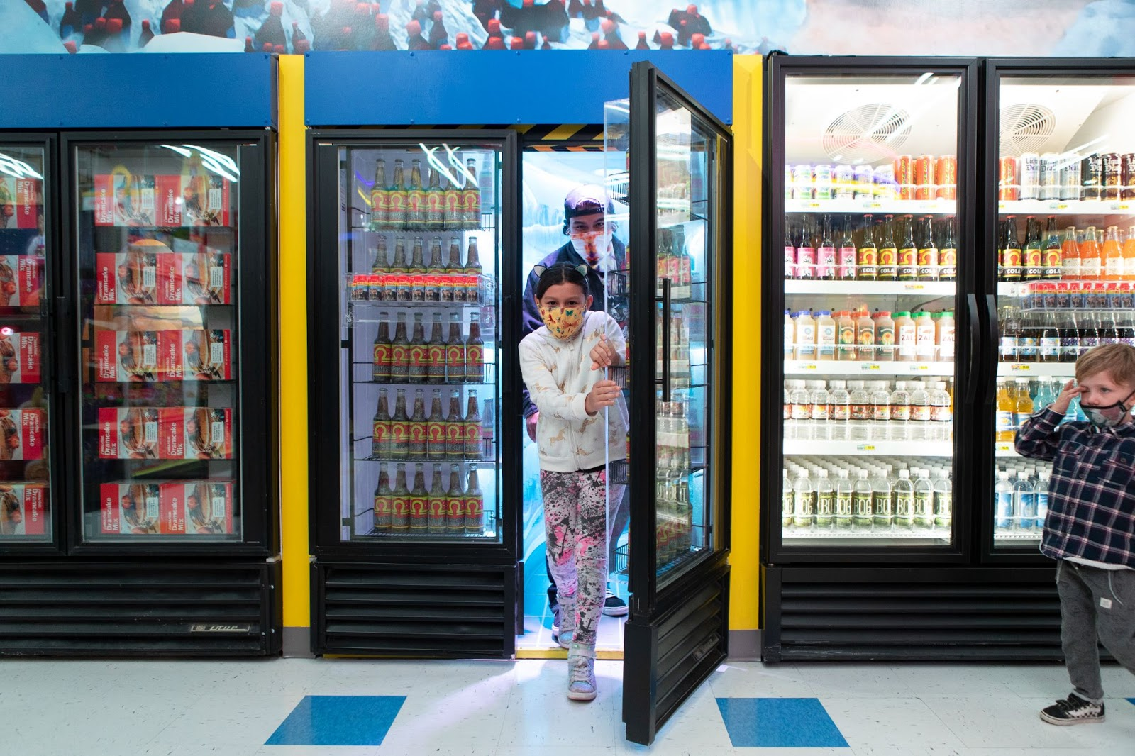 A masked young girl, approximately 8-10 years old, walks out of the drink cooler portal. An adult walks out behind her and there is also a young toddler off to the right next to another drink cooler.