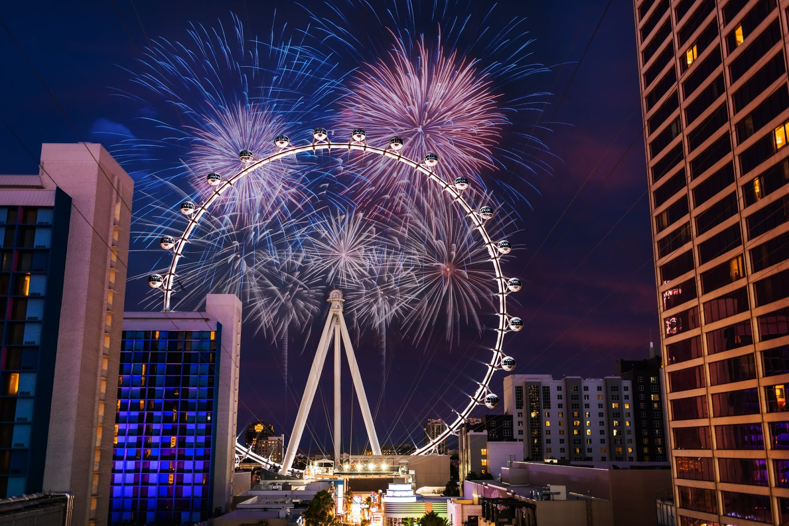 A photo of the largest observation wheel in the world, The High Roller, sits between several hotels at The Linq on The Strip. The High Roller glows in the night as red, white and blue fireworks go off in the background.