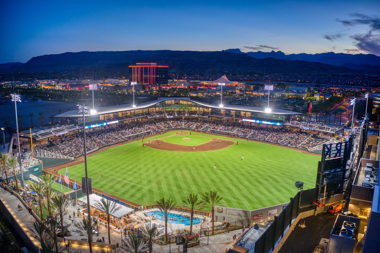 an aerial photo of the Las Vegas Ballpark at sunset. A large hotel and events center can be seen in the background as the sun sets behind the mountains. The stadium is filled with fans as the Las Vegas Aviators, Las Vegas' minor league baseball team, takes the field.