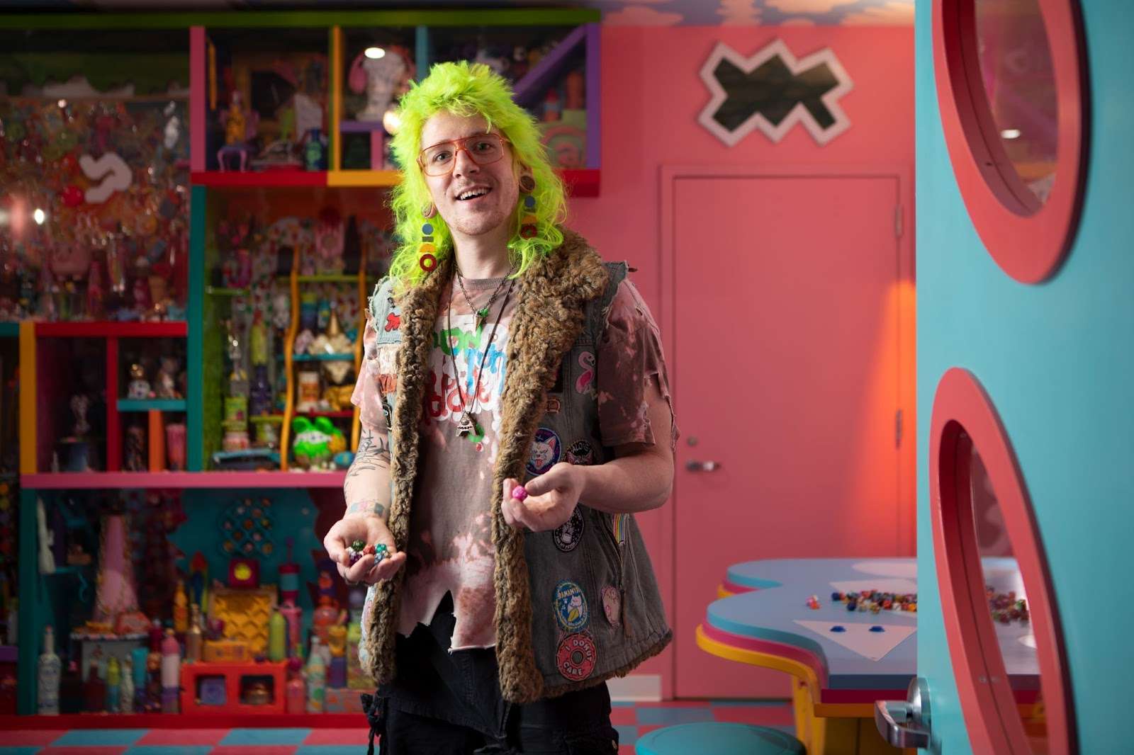 """Kyle Singer with bright green hair, holding small round clay circles inside """"Sa Lawn"""" at Meow Wolf Denver"""