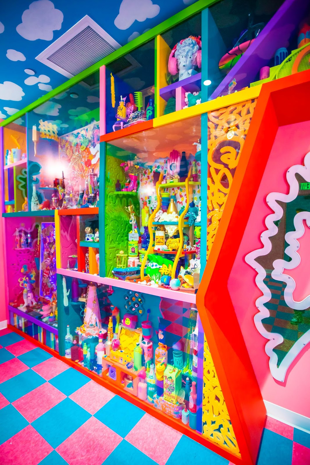 Brightly colored shelves with lots of hair styling products, also brightly colored