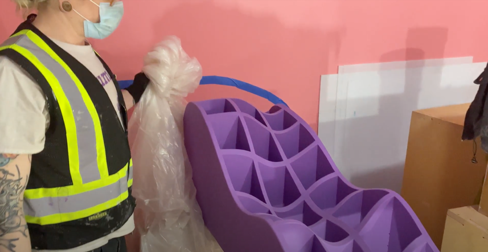 Person in a safety vest and facemark holding a plastic sheet, unveiling a undulating waffle bench inside Meow Wolf Denver