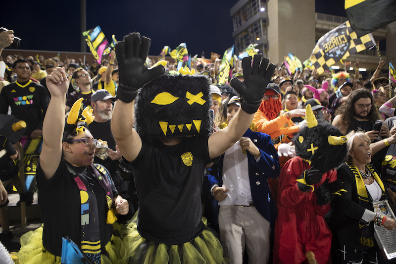 Person with gloves and Snaggy head covering with hands in the air celebrating in the stands