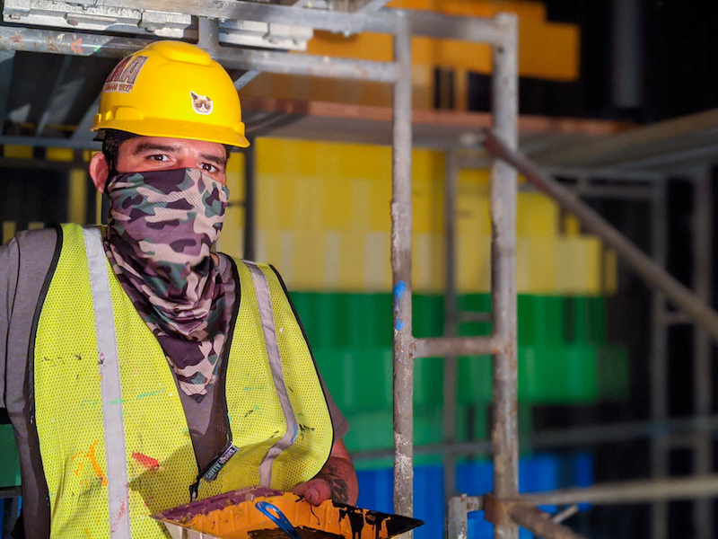 Miguel Rodriguez wearing a yellow hard hat and a face covering in an area under construction at Omega Mart in Las Vegas, NV.