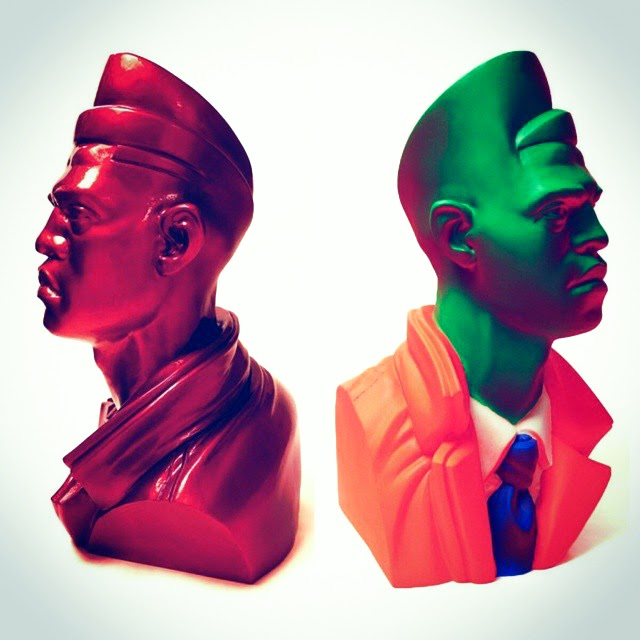 Sculpture of two faces looking in opposite directions, one wearing a shirt and tie and the other wearing a jacket