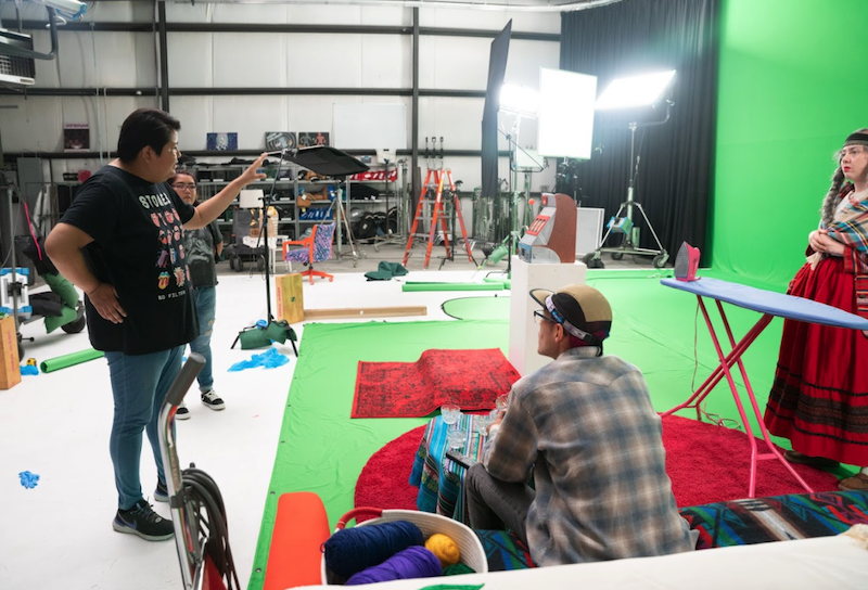 People standing around a green screen area and discussing exhibition content at Meow Wolf Santa Fe