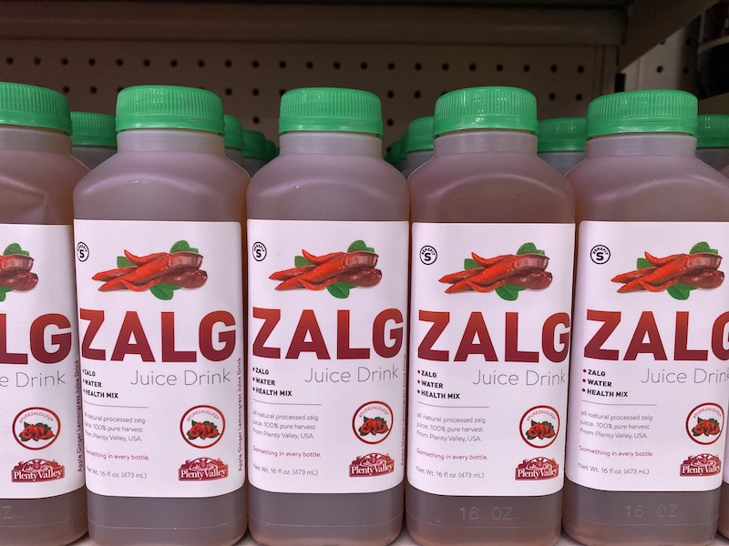 """Image of Zalg an apple juice with on the Omega Mart shelf. The bottle is see through with a light brown liquid. There is a carrot-like vegetable with multiple arms on the label, and ZALG is written in large red letters. The label reads """"Zalg, Water, Heath Mix. All Natural processed zalg juice, 100% pure harvest from Plenty Valley, USA. Something in every bottle. #PureZalgLife"""""""