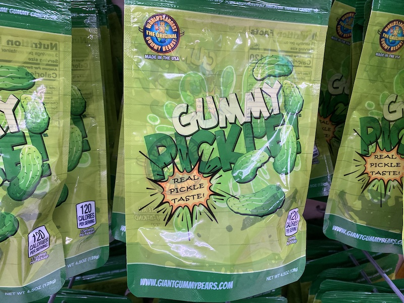 """a green plastic package that has a photo of a large gummy pickle. There are several pickles flying around on the packaging and an exclamation that reads """"REAL PICKLE TASTE!"""""""
