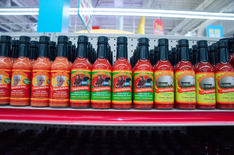 Several Original Family Recipe sauces are displayed on a shelf. In the center is Stepfather's Choice. The flavor is Lonely Habanero. The label is a photo of a man in a cutoff sleeve red flannel shirt leaned against an old sporty car. He has a handlebar mustache and beard. Underneath his photo, the label reads Non-Toxic Vertebrate Sauce.