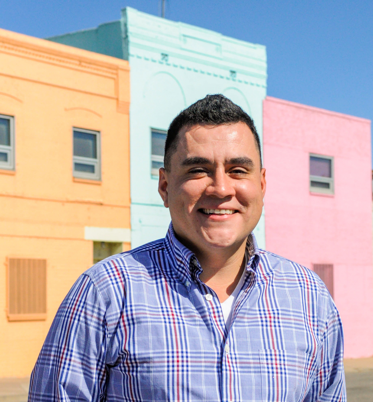 Man in plaid shirt and short dark hair, smiling and standing in front of pastel colored multi-story building