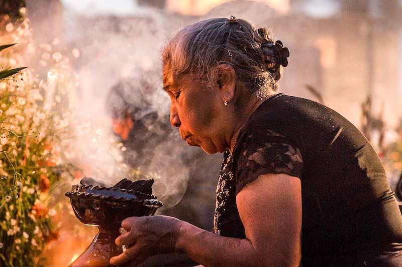 Woman burning Copal incense at an Ofrenda.