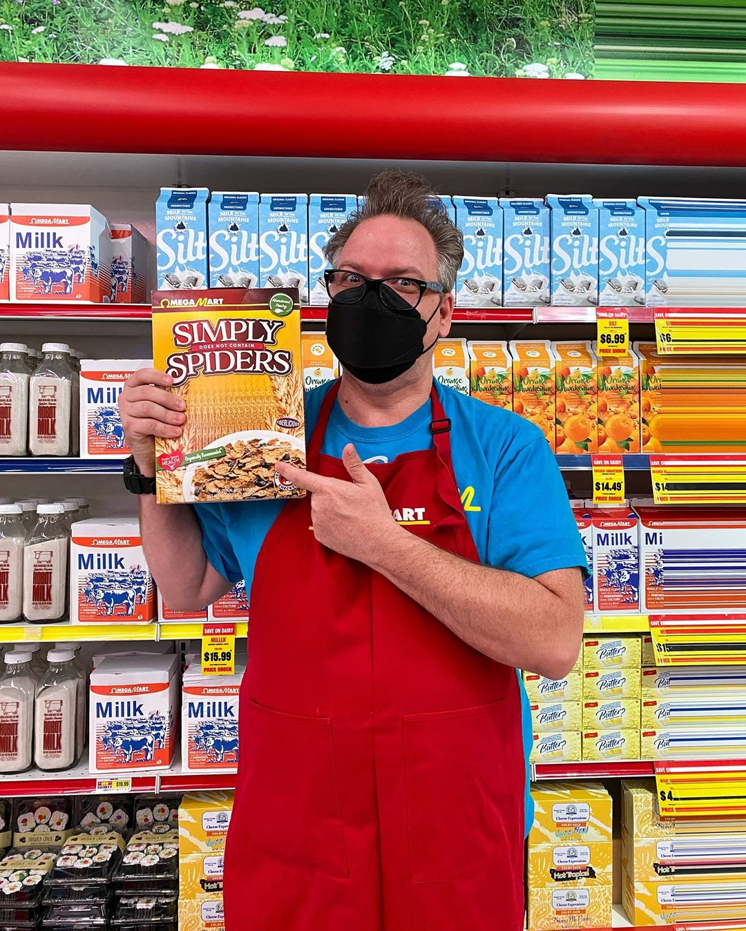 Omega Mart employee with a black mask and glasses, holding a box of Simply Spiders cereal and pointing to it