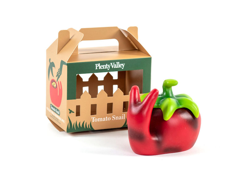 red plastic snail that looks similar to a tomato in front of a box with the words Plenty Valley.The box looks kind of like a fence with a handle on top.