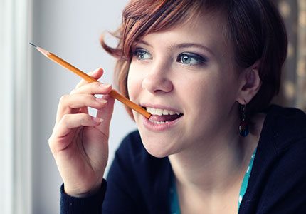 A college student thinking and nibbling on her pencil