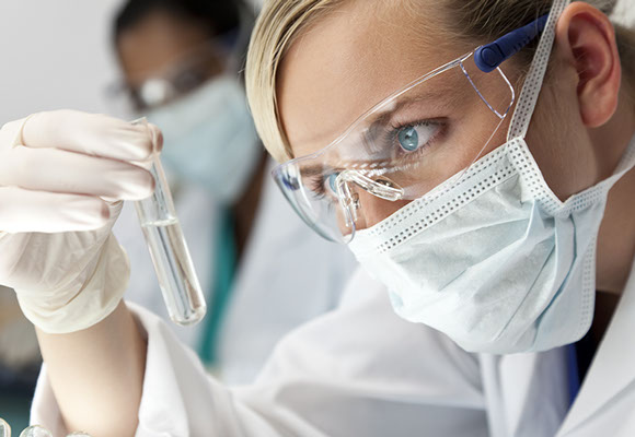Two scientists studying a vial