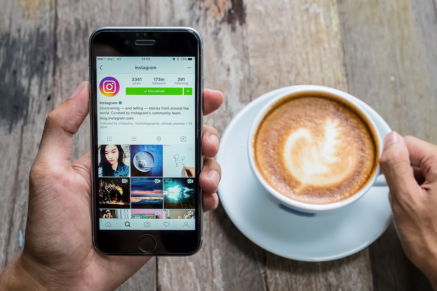Person looking at Instagram while drinking a coffee