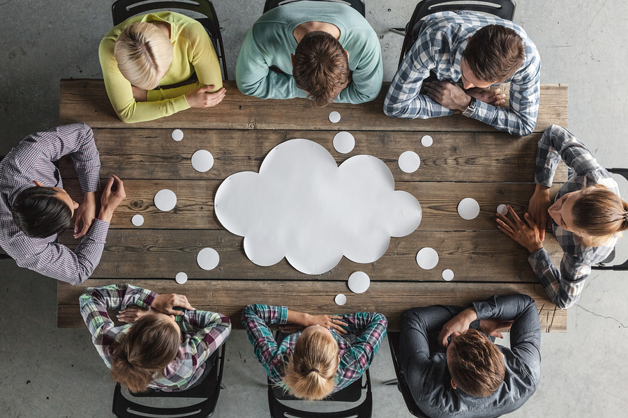 People around a table with a paper cloud in the middle