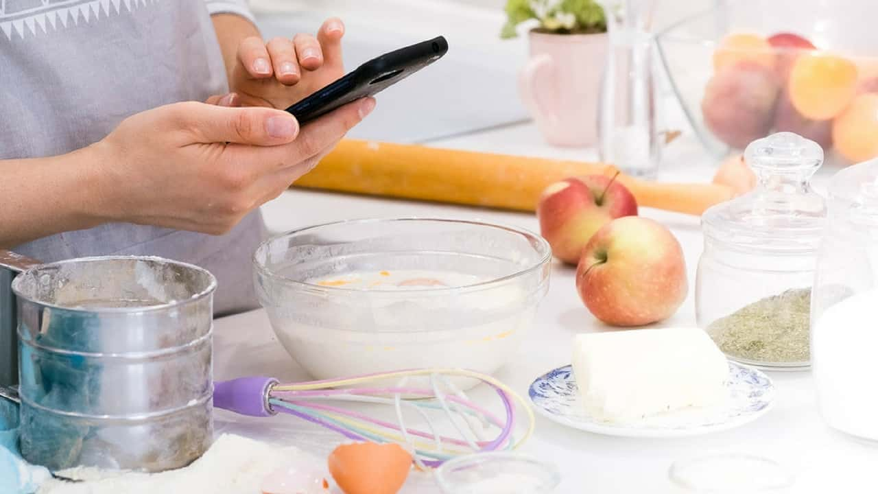 Person using phone while baking