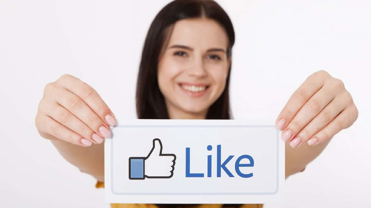 Person holding a poster with a Facebook Like button