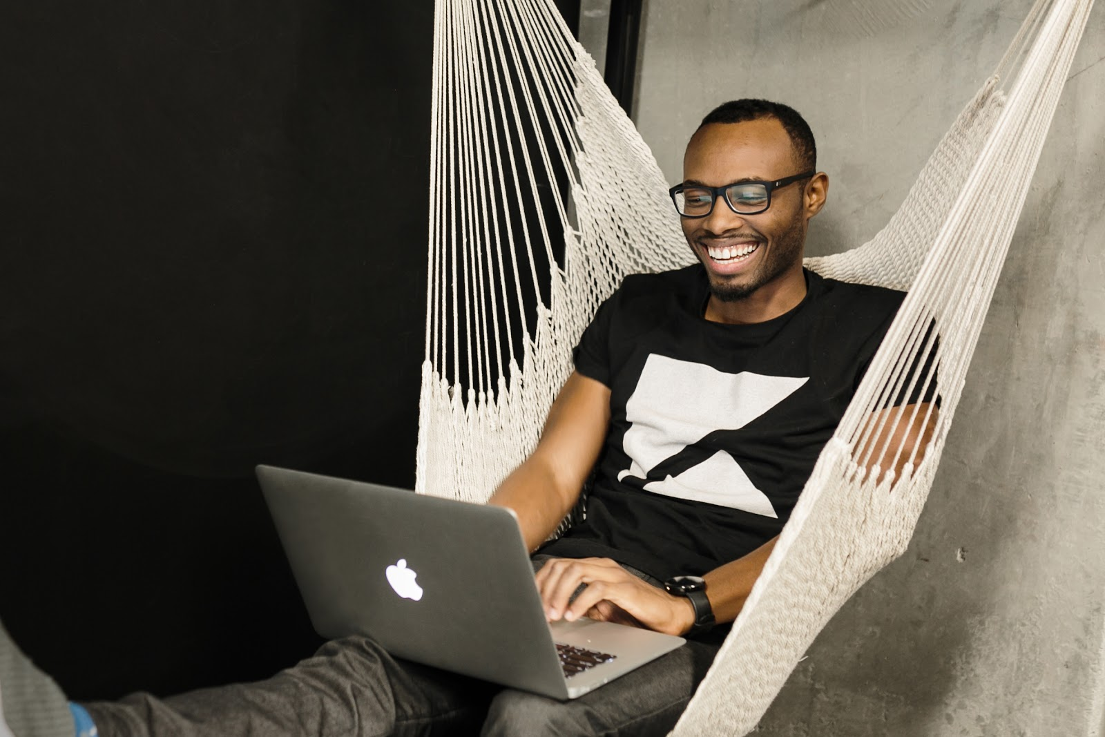 Smiling person in a hammock, working on a laptop