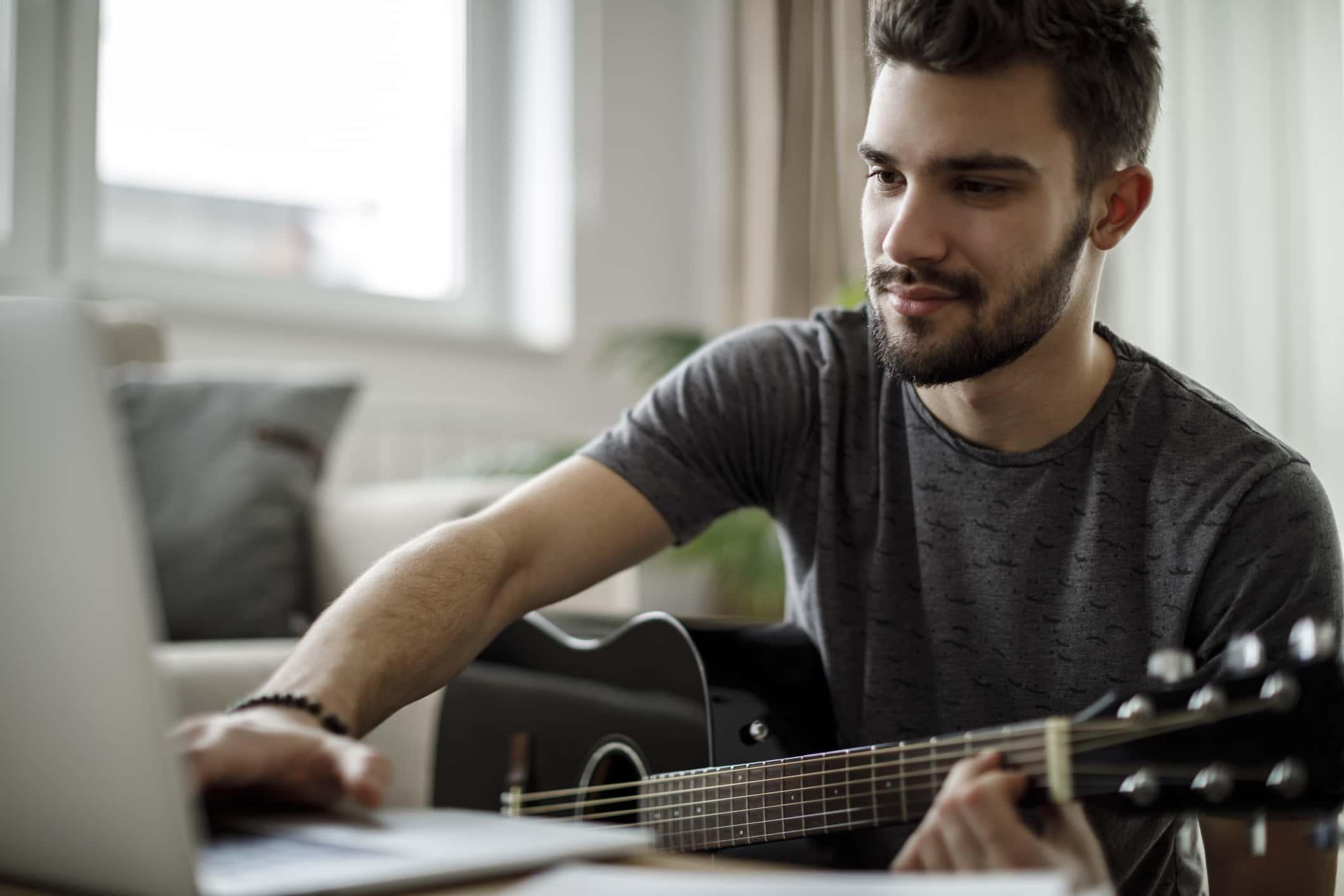 Guitar player teaching an online course