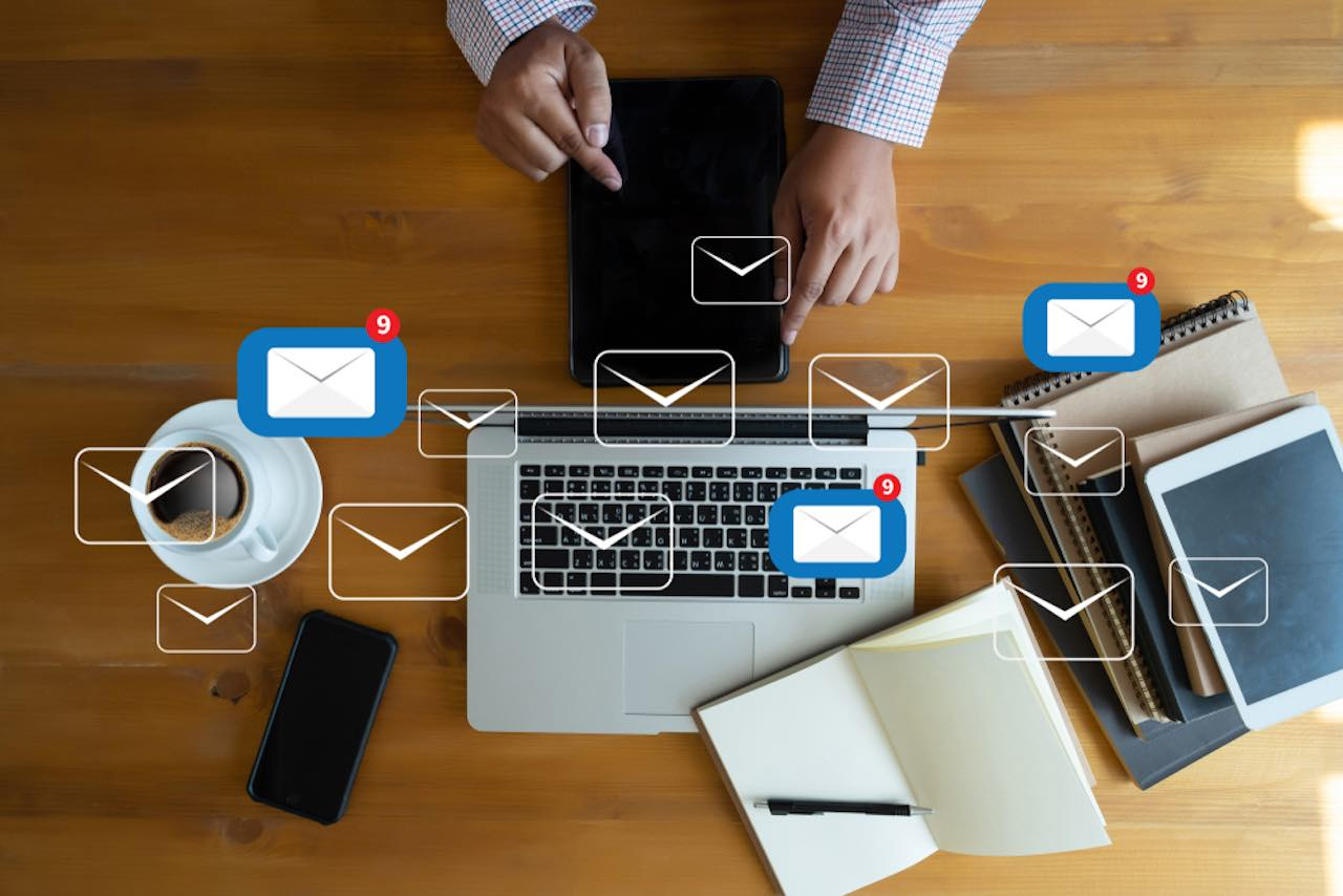 Hands holding a tablet, sitting at table with laptop, smartphone, and stacked notebooks, with email icons floating above
