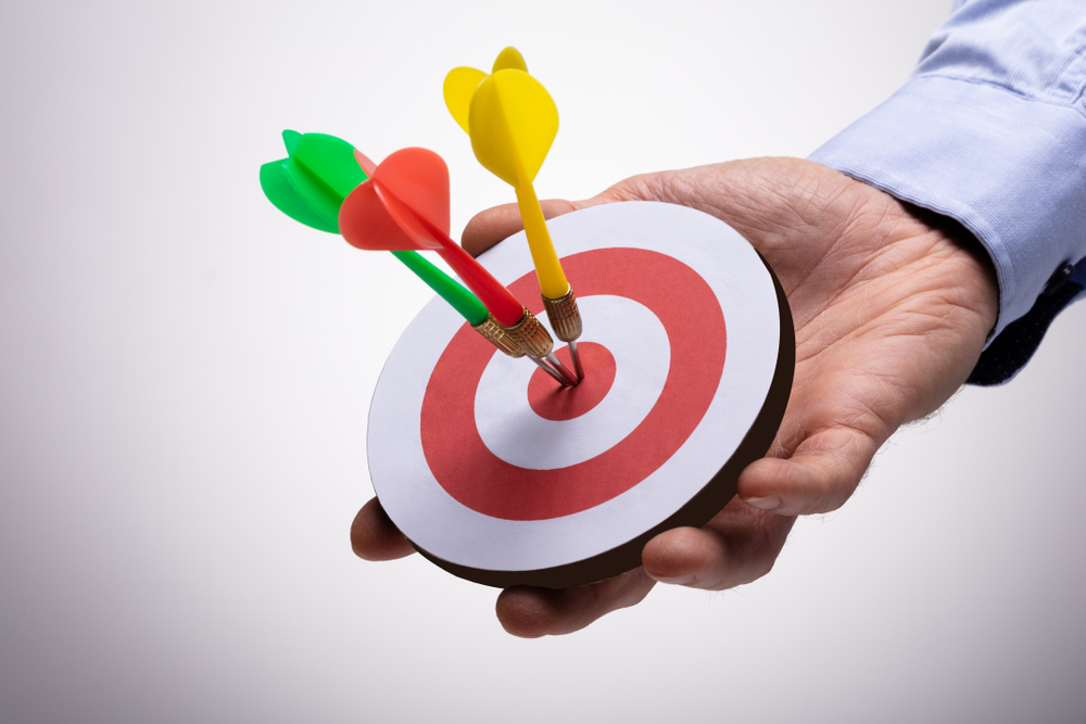 Hand holding small target with three darts in bullseye