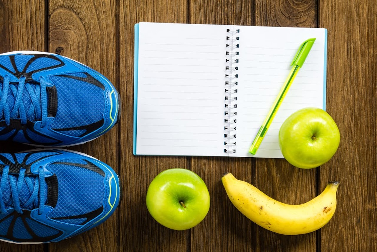 Athletic shoes next to an open notebook with a pen, surrounded by apples and bananas