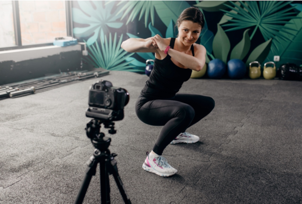 Female personal trainer recording video for online fitness coaching demonstrating exercises
