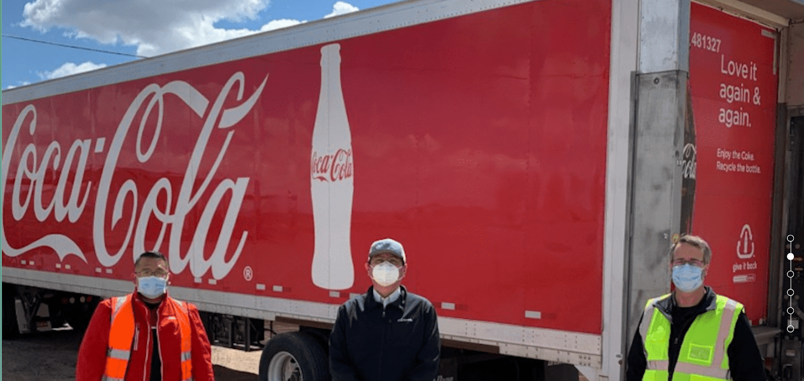 3 people standing in front of a Coca-Cola truck