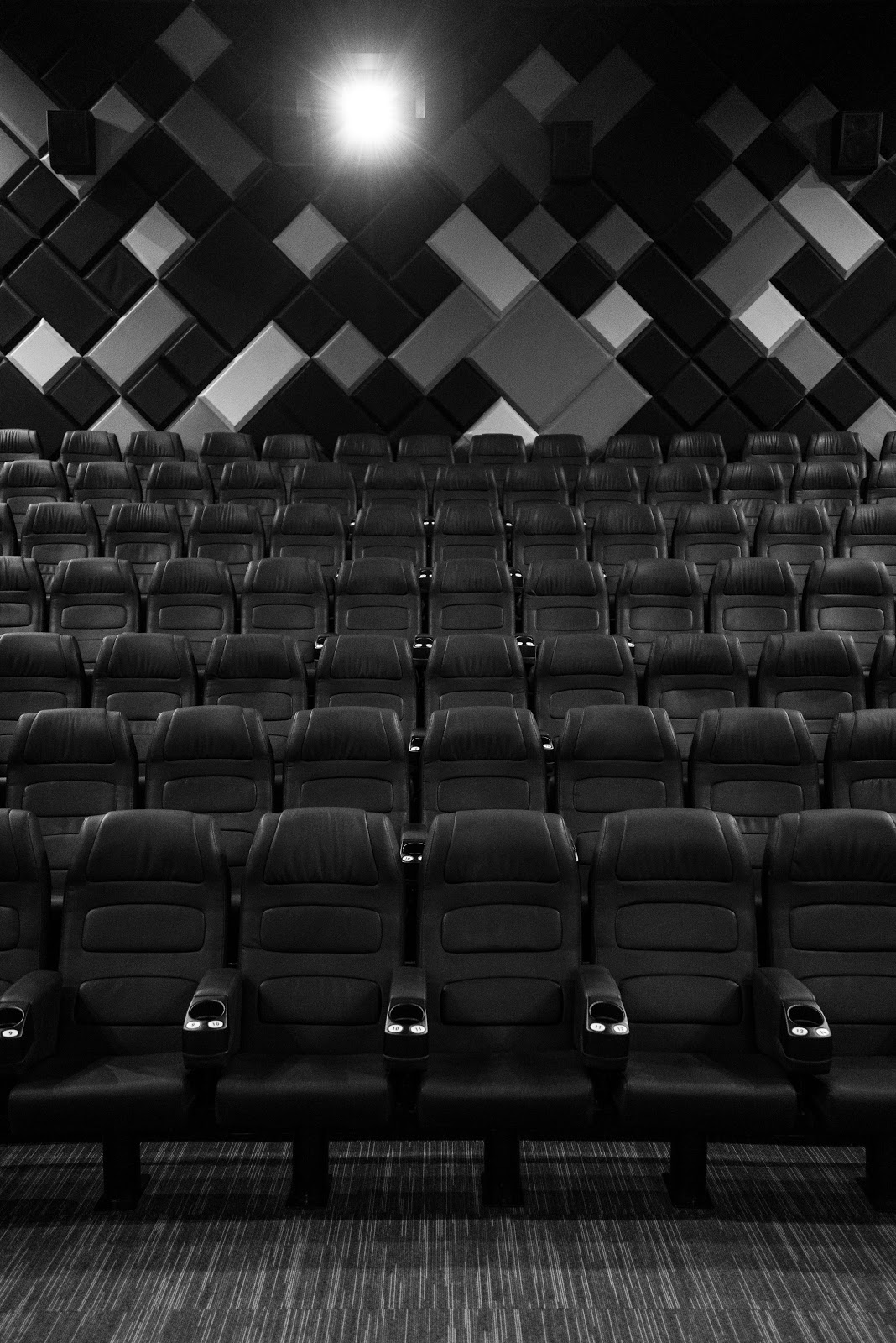 Black and white photo of an auditorium with audio panels at the back wall behind the rows of seats