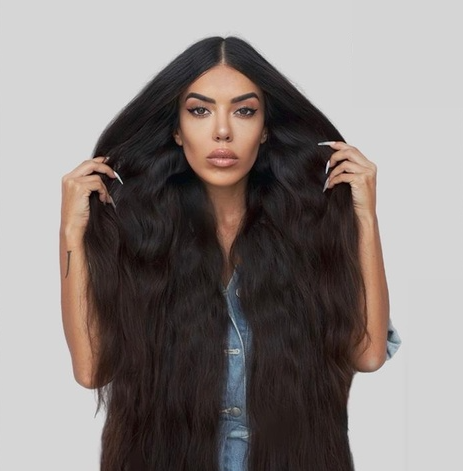 Photo of Sara Revuelta showcasing her long hair against a grey background