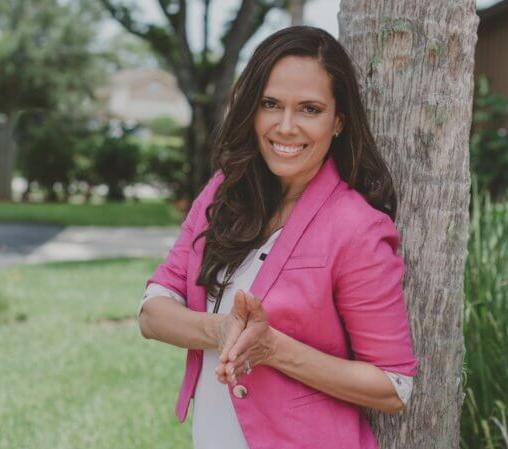 An image of Carla Sanchez smiling wearing a pink vla