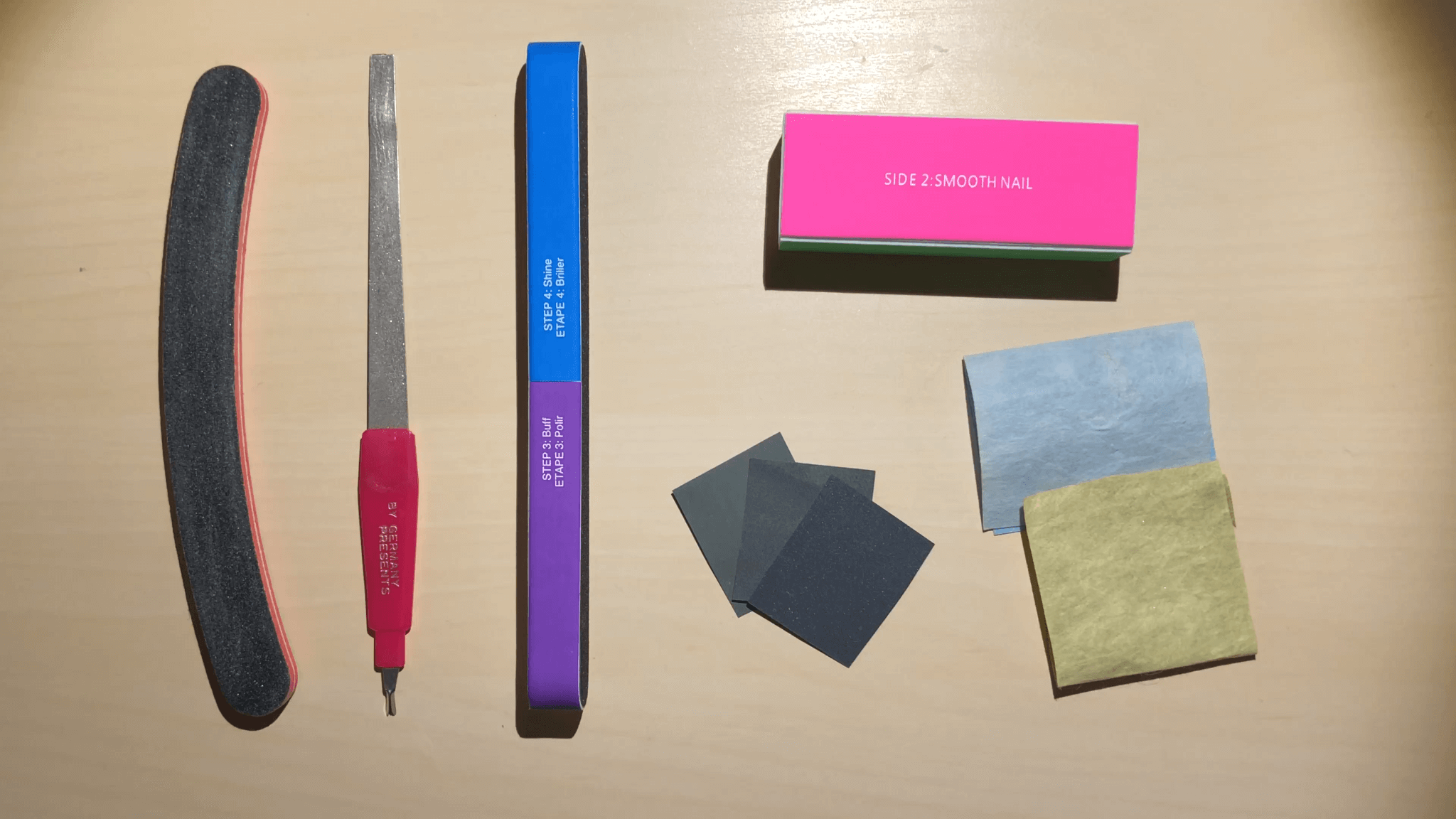 A few tools you can use for shaping your nails including a metal file, multi-sided buffer, and polishing papers.