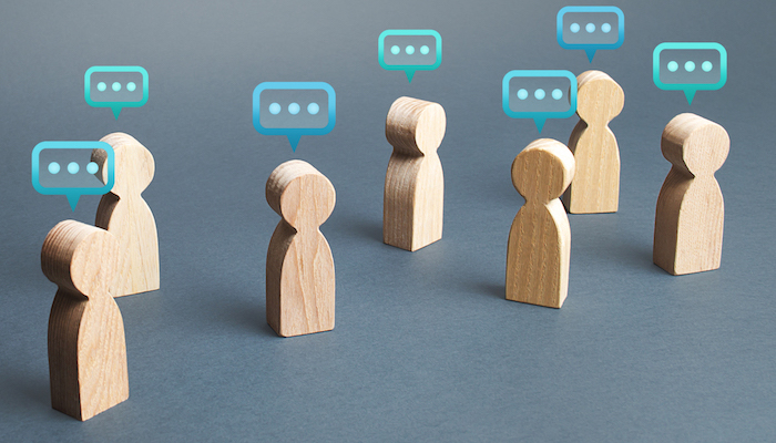 Wooden figurines with chat bubbles above them
