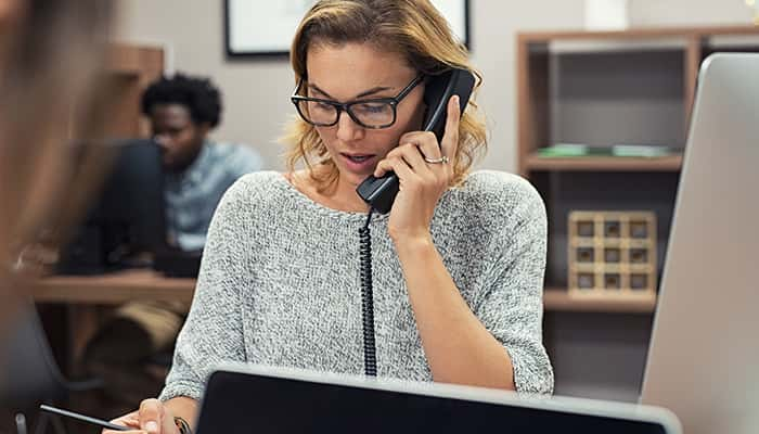 Insurance agent answers office phone.