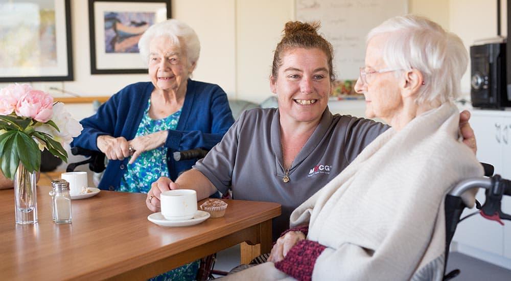 senior ladies having tea with aged care staff