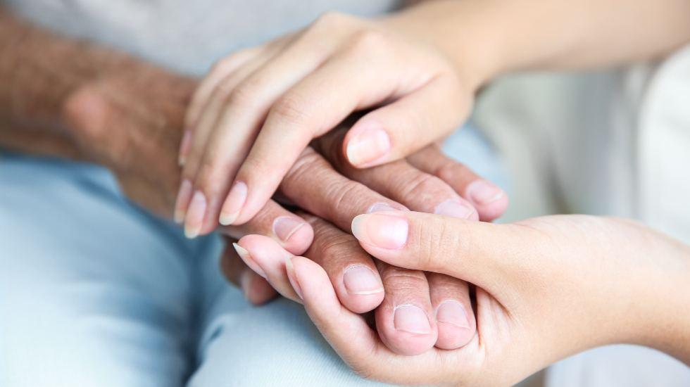 Carer holding hands of an elderly patient
