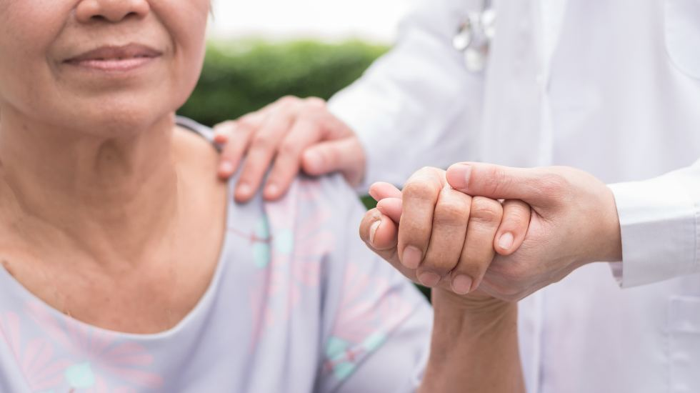 Patient holding doctor's hand